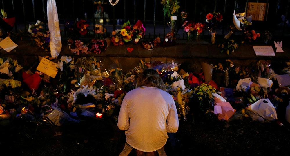 Un hombre reza cerca de la ofrenda floral a los víctimas del atentado en Christchurch, Nueva Zelanda