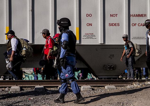 Seguridad privada vigila a migrantes frente a un tren de carga. En la ruta migrante se encontraron al menos cuatro de estas empresas dedicadas a la custodia de las vías, que también ejercen funciones de migración y seguridad pública.