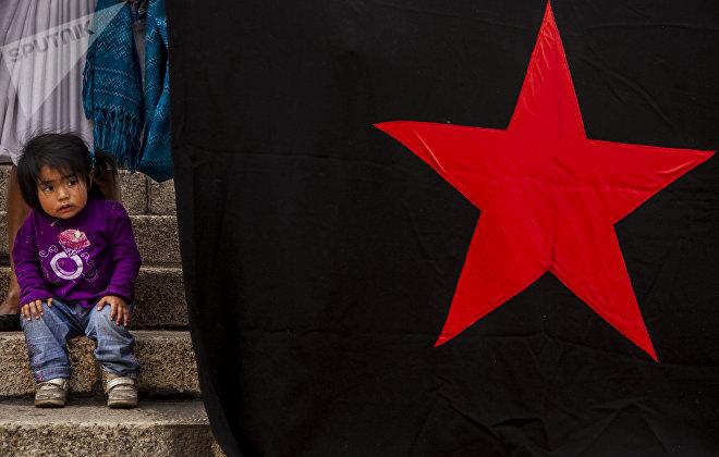 Ciudad de México. Niña junto a una bandera con la estrella roja en una manifestación en solidaridad con las huelgas en Matamoros.