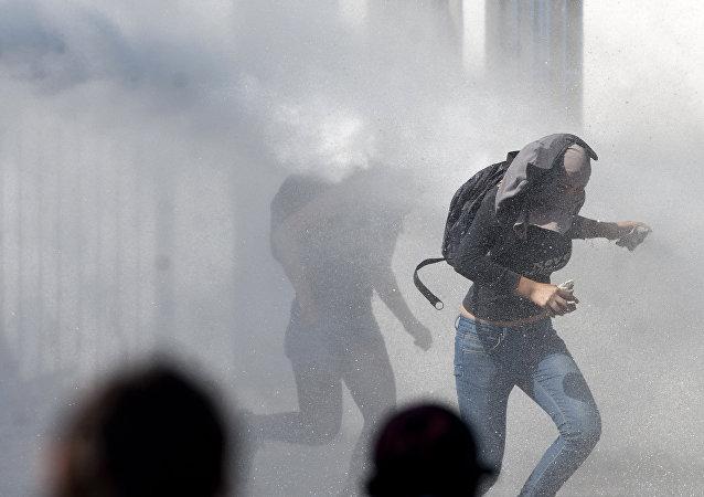 Manifestantes corriendo de la represión policial en el Día del Joven Combatiente de 2012 en Chile.