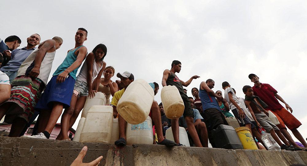 Venezolanos rellenan botellas de agua en Caracas