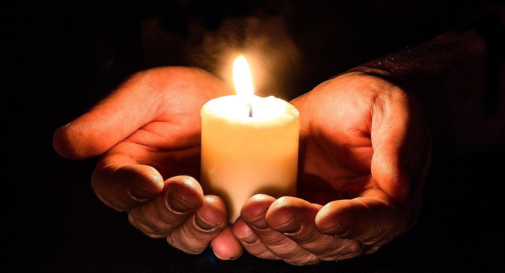 Manos sosteniendo una vela en una vigilia