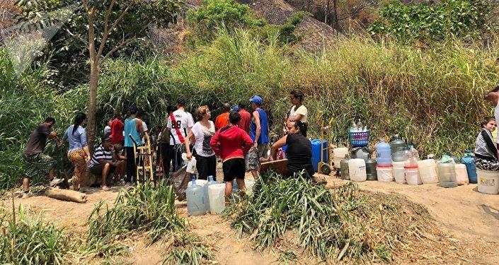 En ocasiones, la gente que espera por llevar agua a sus casas intercambia opiniones sobre la coyuntura venezolana