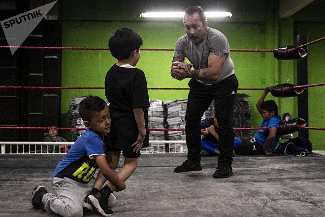 Ecatepec, Estado de México: Tigre Metálico y dos alumnos durante la clase de lucha libre en la Arena Rey Bucanero