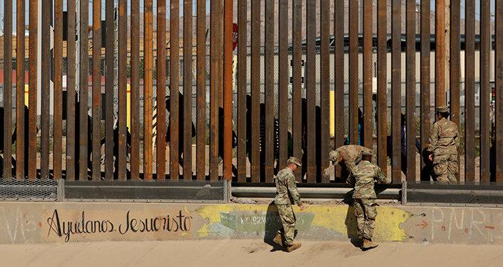Militares estadounidenses custodian un trecho de la frontera entre EEUU y México entre El Paso y Ciudad Juárez, mientras transitan migrantes
