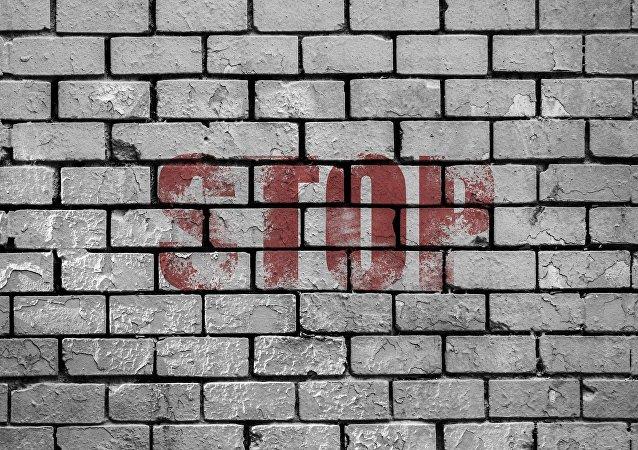 Una pared de ladrillos con palabra 'stop'