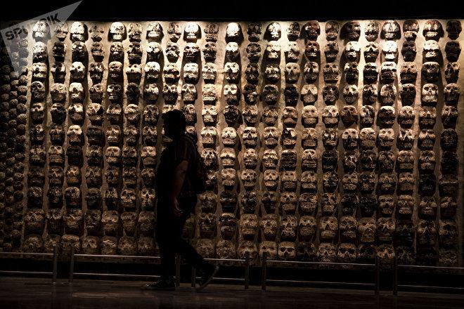 Turista frente a la representación del Tzompantli, una de las 15.000 piezas encontradas en el recinto sagrado