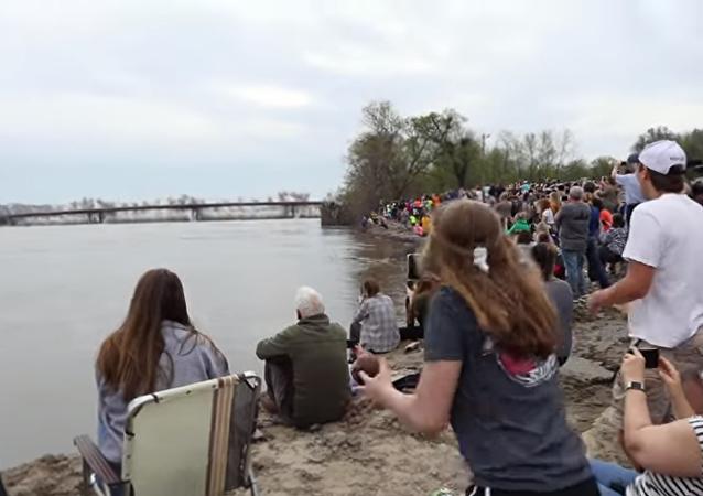 La gente se reúne para ver la demolición de un puente sobre el río Misuri