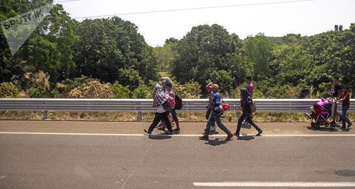 Miembros de la caravana migrante caminan sobre la carretera México 200