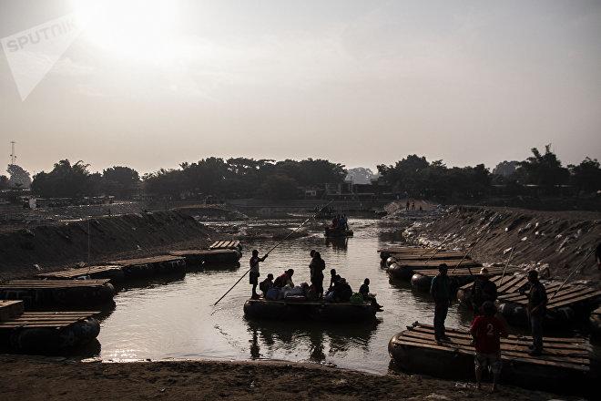 Suchiate, Chiapas: Migrantes cruzan en balsa el río Suchiate