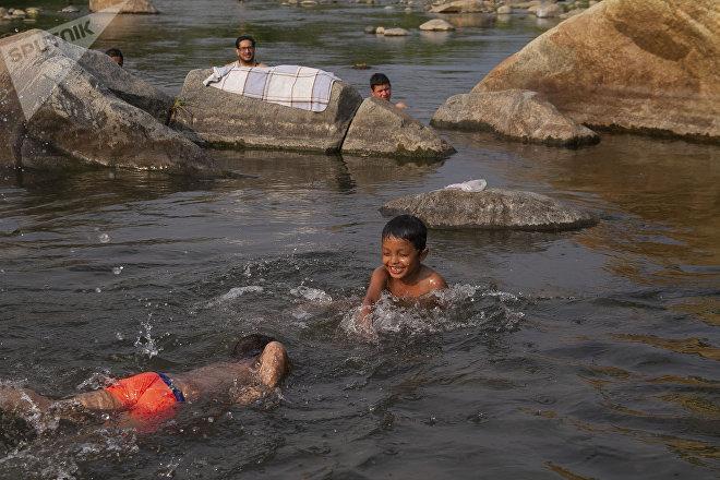 Huixtla, Chiapas: Niños del éxodo centroamericano se divierten en el rio Huixtla