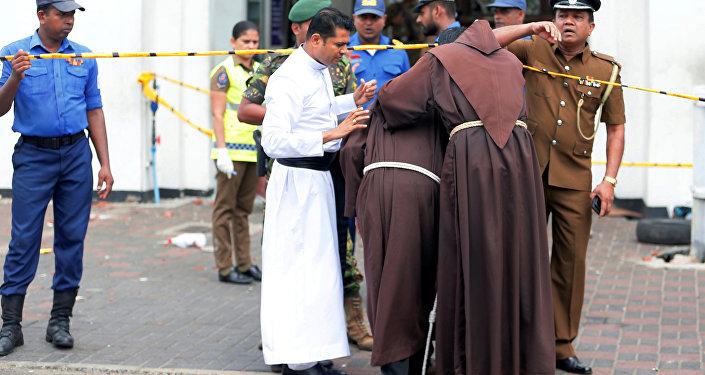 Unos sacerdotes entran en la iglesia de San Antonio de Kochchikade tras las explosiones