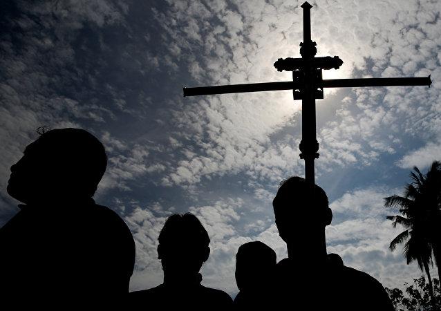 Un hombre sostiene una cruz durante un entierro masivo de víctimas en Sri Lanka