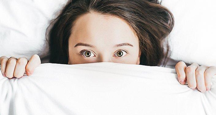 Mujer se asoma por las sábanas de una cama