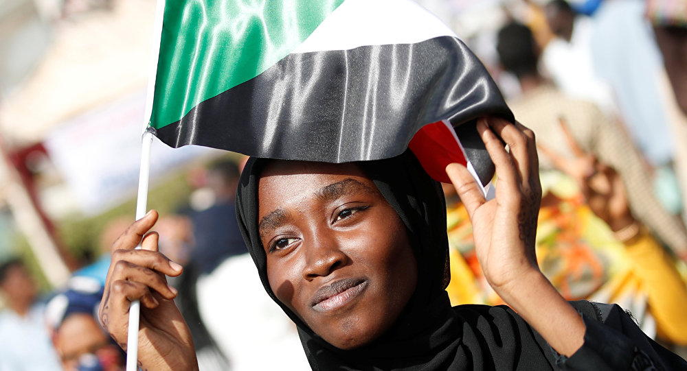 Una mujer con la bandera de Sudán