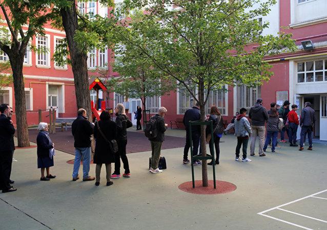Electores esperan afuera de un colegio electoral en Madrid
