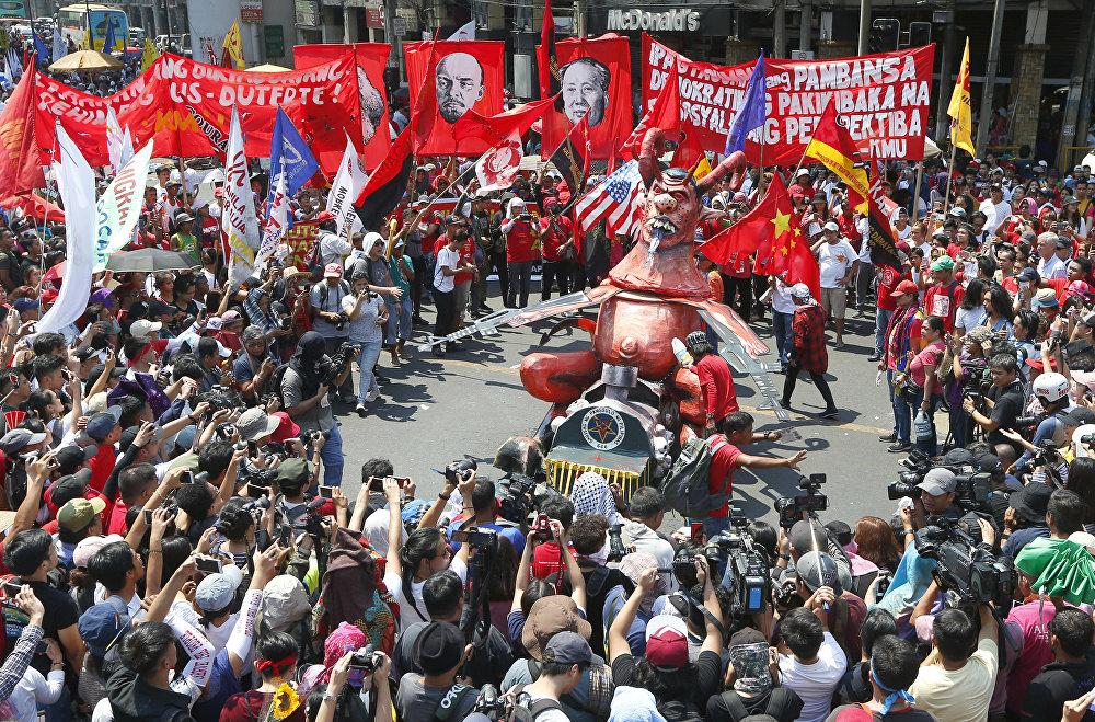 Trabajadores filipinos se preparan para quemar un muñeco que encarna al presidente Rodrigo Duterte porque, según ellos, el mandatario no cumple con sus promesas de campaña
