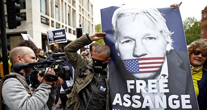Activistas con la foto de Julian Assange, fundador de WikiLeaks