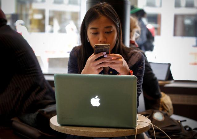 Una mujer con un Macintosh y un iPhone