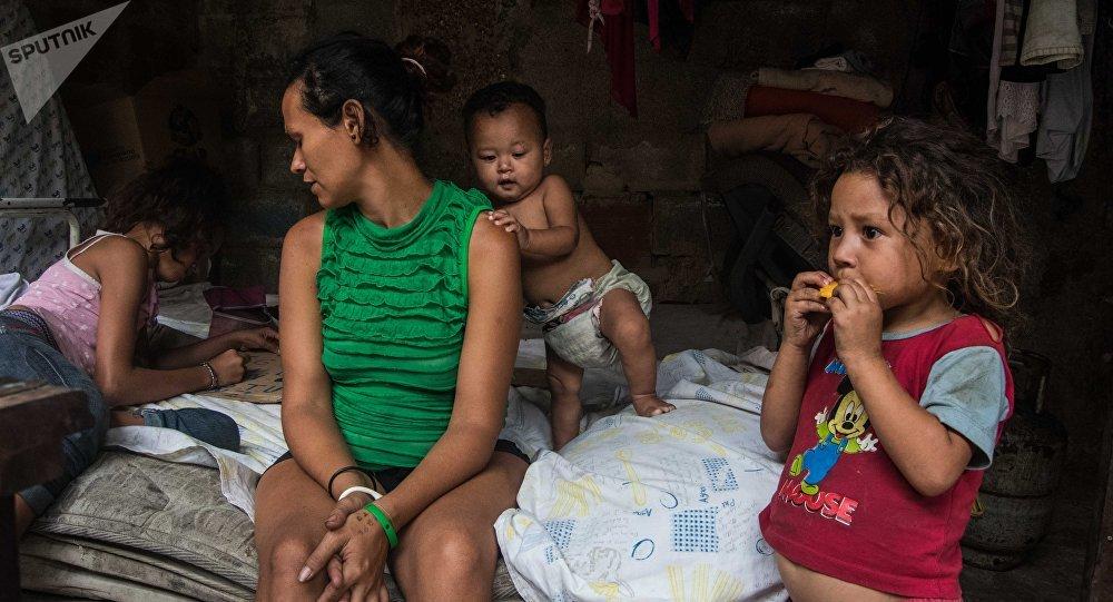 La mujer venezolana de la comunidad 27 de Febrero con sus hijos