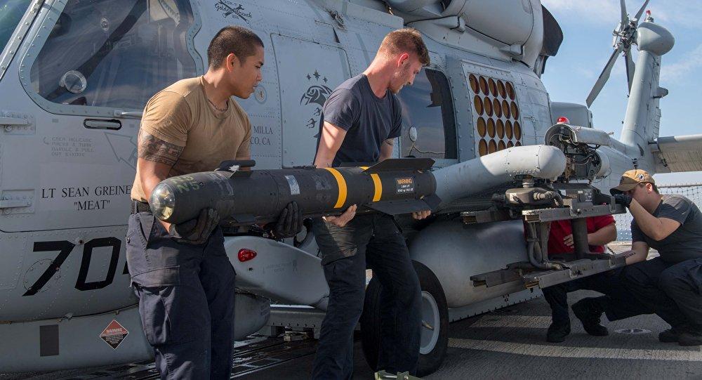 Los militares estadounidenses instalan un misil Hellfire en un helicóptero