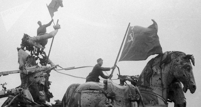 Soldados alzan las banderas soviéticas sobre la Puerta de Brandenburgo