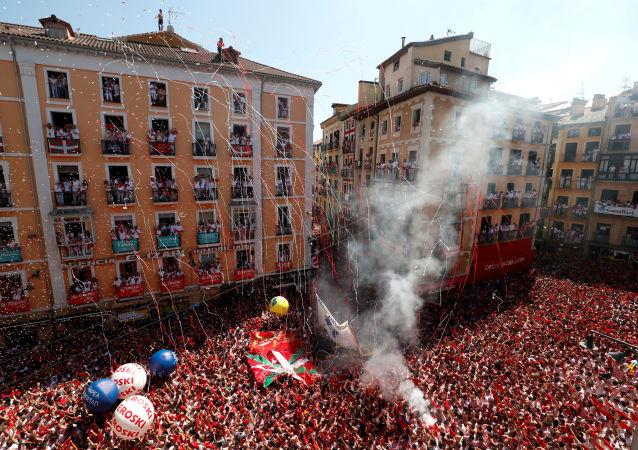 Participantes de San Fermín sostienen las tradicionales bufandas rojas durante el 'chupinazo' que inaugura la fiesta en Pamplona, España.
