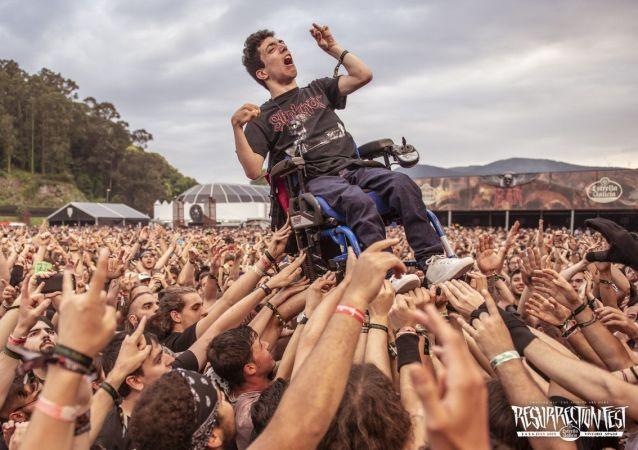 Decenas de jóvenes levantan la silla de ruedas de un muchacho con parálisis cerebral, para que pudiera ver al concierto del grupo Trivium en el festival  Resurrection Fest