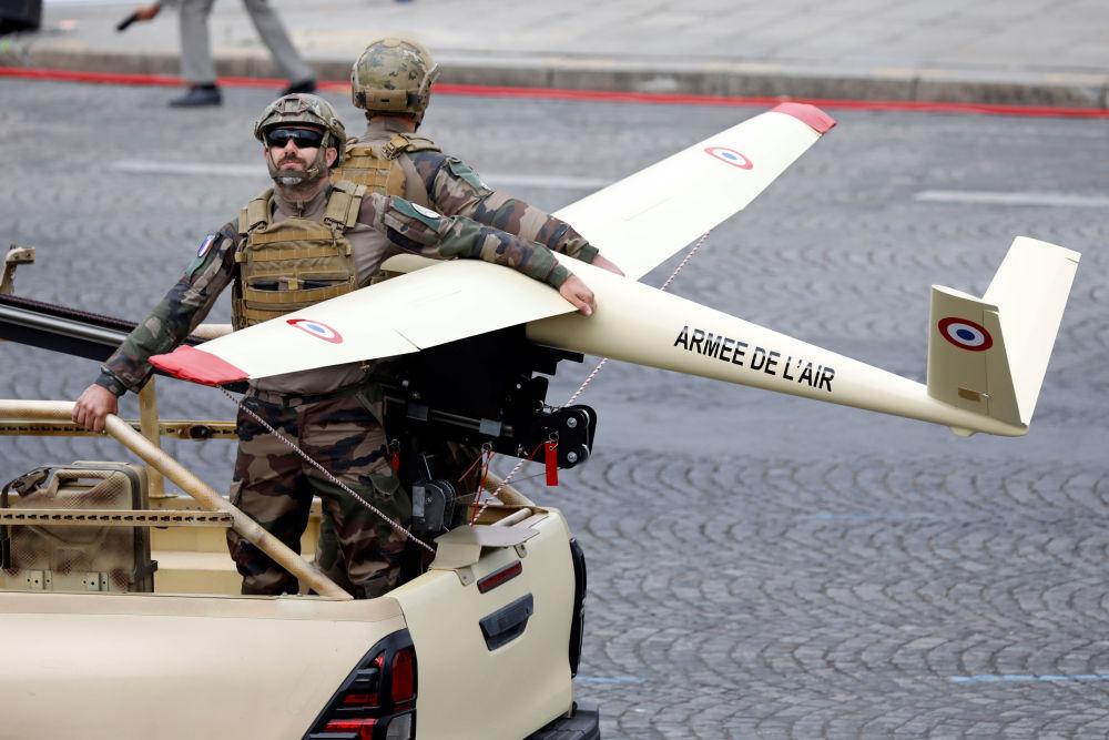 Participantes del desfile militar con un dron en los Campos Elíseos de París.