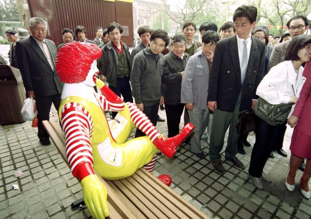 Unos chinos pasan al lado de una estatua de McDonalds
