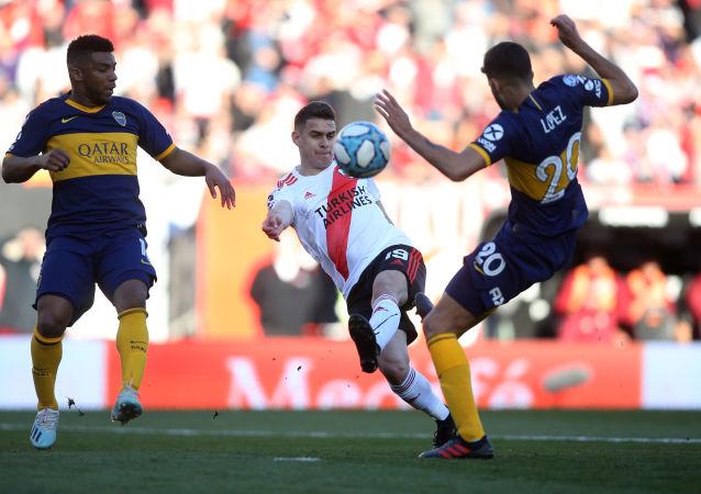El futbolista de River Plate Rafael Santos Borré disputa el balón con Lisandro López de Boca Juniors