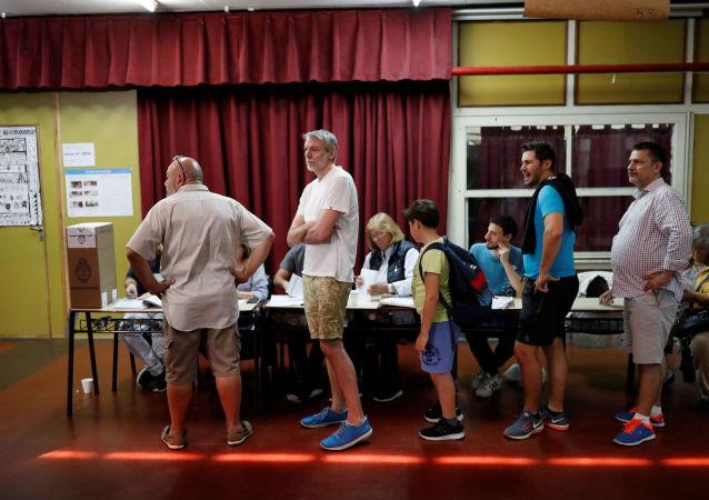 Argentinos hacen cola para emitir sus votos en un colegio electoral, en Buenos Aires