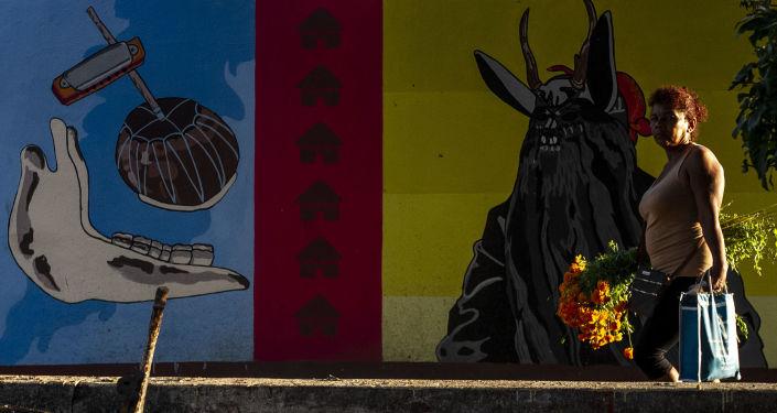 Pobladora camina durante el Día de Muertos frente un mural referente la danza de los diablos