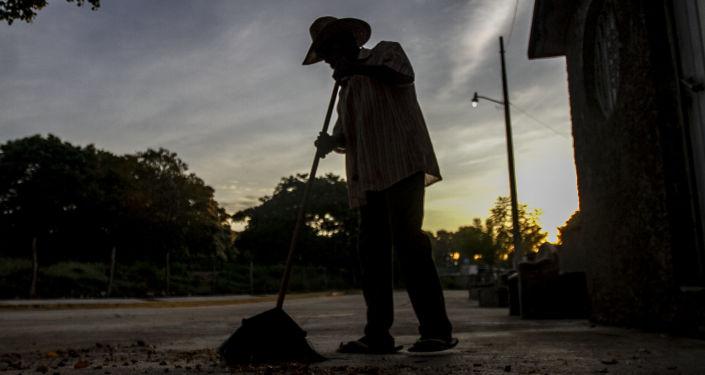 Panteonero limpia la entrada del cementerio del pueblo para recibir la danza de los diablos durante el Día de Muertos