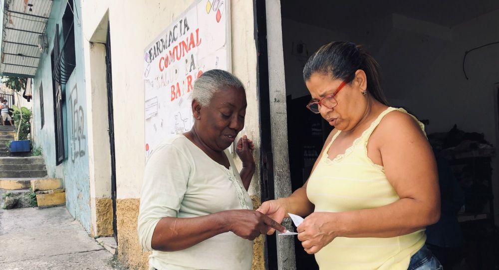 Manuela, dueña de la casa donde está la farmacia comunal, entregando unos medicamentos a una vecina del barrio