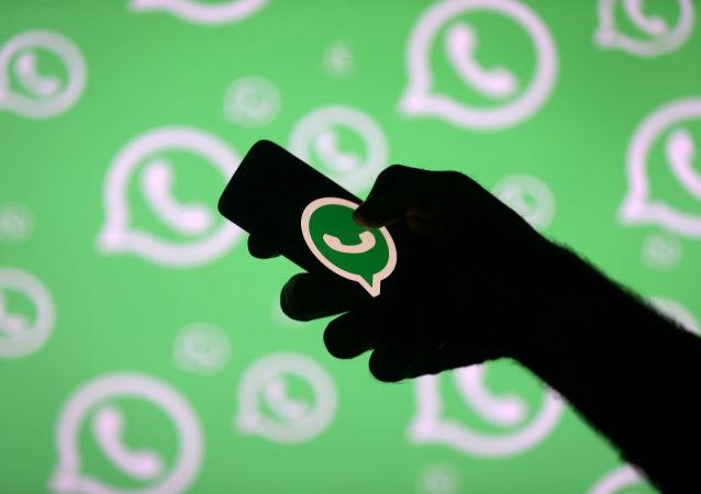 Una persona posa con un teléfono inteligente delante de una pared con el logotipo de WhatsApp