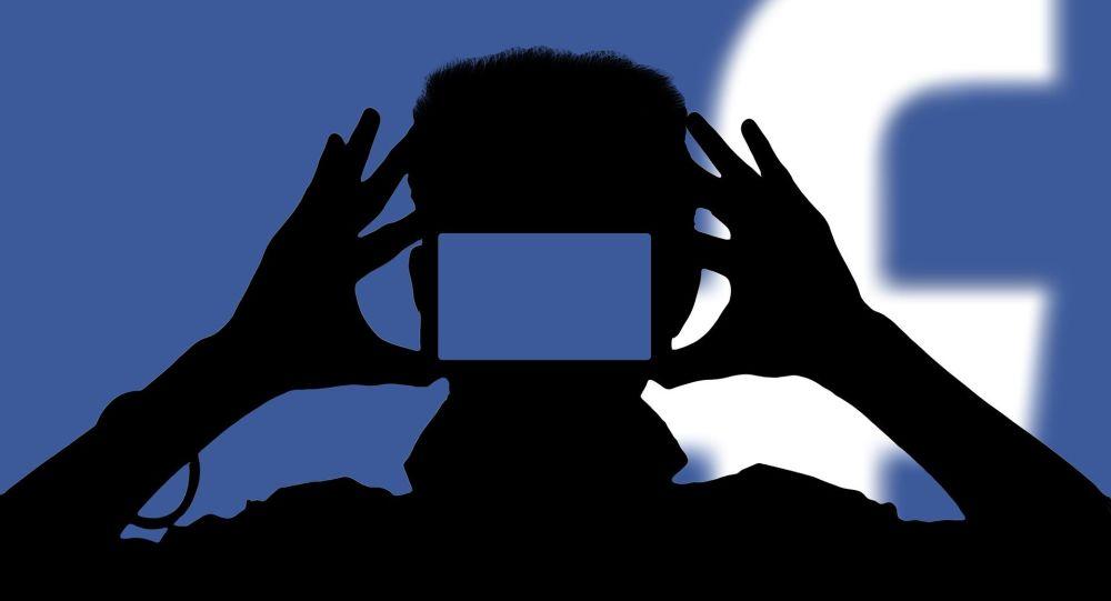 Una persona con un teléfono móvil con el logo de Facebook de fondo