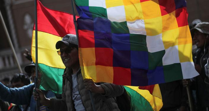 La bandera wiphala y la tradicional de Bolivia alzada por un manifestante durante una marcha en La Paz en apoyo a Evo Morales, noviembre de 2019