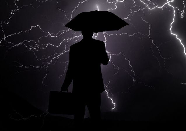 Los rayos y la sombra de una persona con paraguas