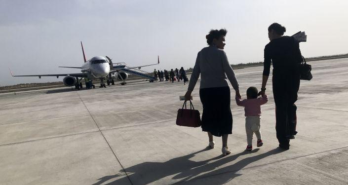 Una familia de uigures en el aeropuerto chino de Kuqa