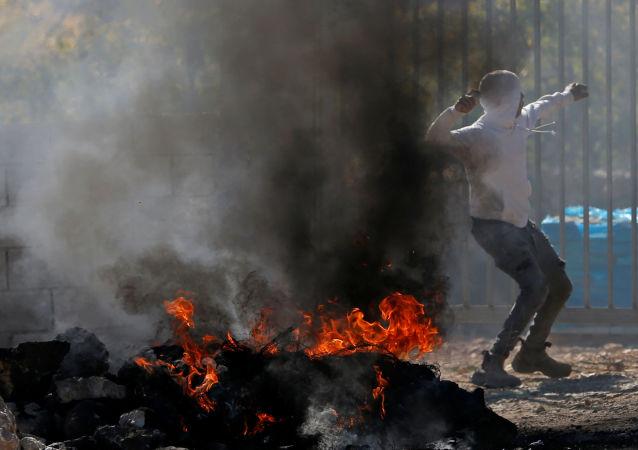 Un manifestante lanza la piedra durante protestas contra la demolición de los edificios palestinos