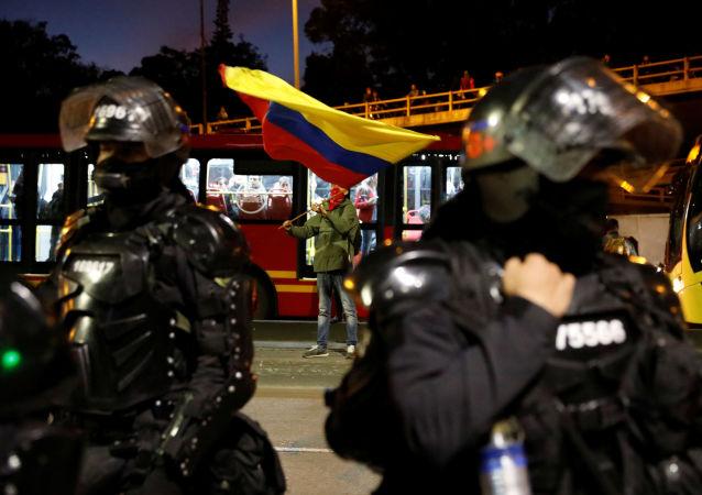 Policías colombianos custodian una calle de Bogotá frente a manifestantes