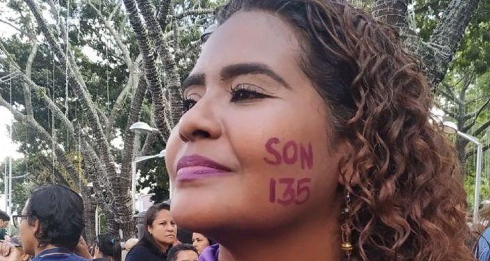 Manifestante señala el número de feminicidios en Venezuela