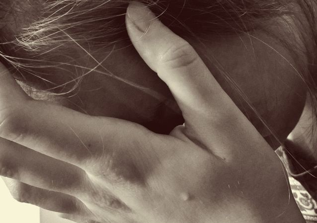 Mujer triste se cubre el rostro - imagen referencial