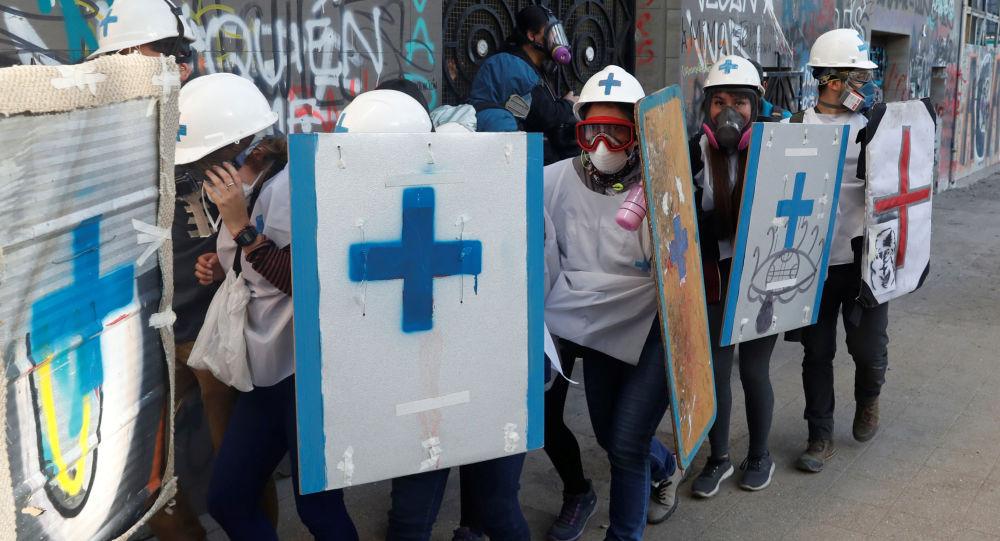 Paramédicos se protegen durante las manifestaciones de protesta en Chile