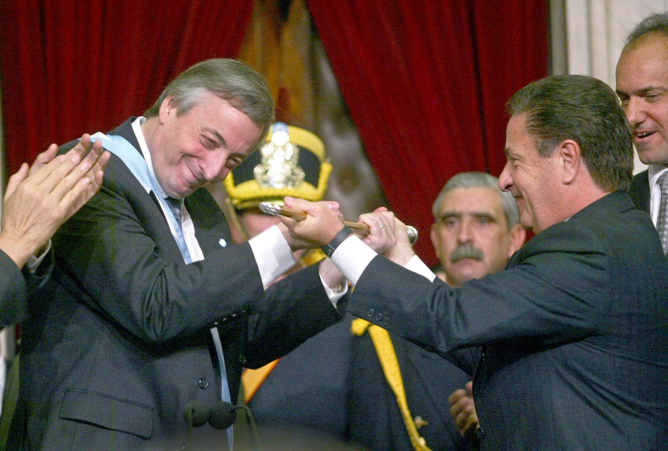 El presidente entrante Néstor Kirchner recibe el bastón presidencial del saliente Eduardo Duhalde, el 25 de mayo de 2003