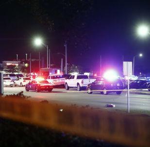 Una fila de vehículos y un camión de UPS se ven detrás de la cinta policial tras un tiroteo en Miramar, Florida