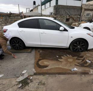Un palestino examina su coche con los neumáticos rajados en Jerusalén Este