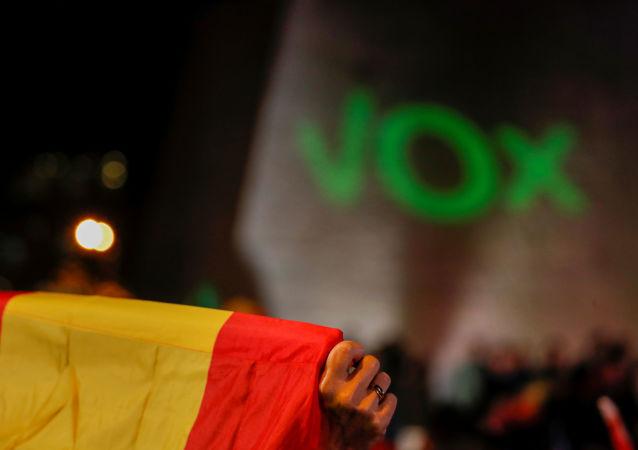La bandera de España con el letrero de Vox al fondo