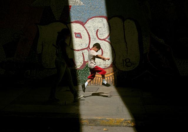 Niño atraviesa espacio iluminado por el sol entre áreas de sombra